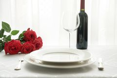 Valentines day table place setting with bouquet red roses, and wine. Valentines day or birthday table place setting with bouquet red roses, and wine. Catering royalty free stock images