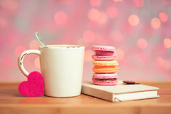 Valentines day breakfast. Tasty breakfast. Cup of coffee with colorful sweets, book and felt heart closeup over christmas lights. Selective focus Royalty Free Stock Photography