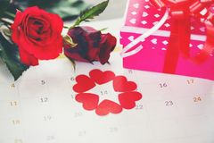 Valentines day calendar love time concept ed heart on February 14 of Saint Valentine`s day pink gift box and red roses flower royalty free stock images