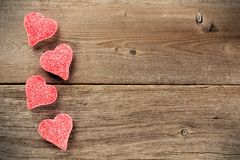 Valentines Day candies on wood background. Heart shaped Valentines Day candy side border on a wooden background Royalty Free Stock Images