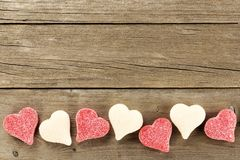 Valentines Day candy border on wood background. Heart shaped Valentines Day candy bottom border on a wooden background Royalty Free Stock Photography