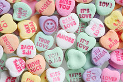 Valentines day candy hearts. Abundance of sweet candy  love messages printed on hearts extremely close-up Stock Photo