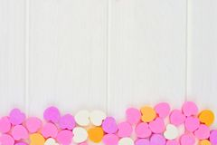 Valentines Day candy hearts bottom border over white wood Stock Photo