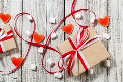 Valentines Day candy hearts marshmallows and box of gifts in craft paper over white wooden background.  stock image