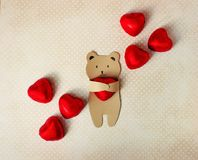 Congratulations on the Valentine`s Day. A small bear of kraft paper holds in his paws a chocolate candy in the form of a stock photography
