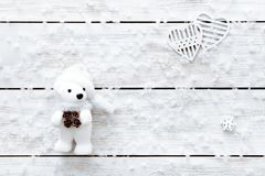 Valentines day card, snowflakes, hearts and toy bear on light wooden table, white flakes of snow on xmas desk, merry Christmas hol royalty free stock image