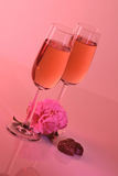 Valentines Day Celebrations. Two glasses of champagne with two chocolates and a pink flower Royalty Free Stock Images