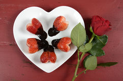 Valentines Day chocolate dipped heart shaped strawberries with rose Stock Photo