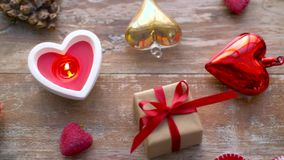 Valentines day or christmas decorations on table. Valentines day, christmas and decoration concept - gift box and red heart shaped candle burning on wooden table stock video footage