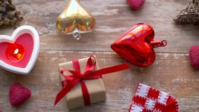 Valentines day or christmas decorations on table. Valentines day, christmas and decoration concept - gift box and red heart shaped candle burning on wooden table stock footage