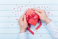 Valentines day or Christmas greeting card. Man holds a gift box in hands. Top view. Flat lay style. Royalty Free Stock Images