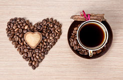 Valentines day coffee and cinnamon. Cup of Coffee and grains in shape of heart with cookie on it and cinnamon bark wrapped with red ribbon on the saucer Stock Photography