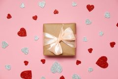 Valentines day composition : gift box packed in kraft paper with ribbon bow and red and grey heart shaped valentines card lay on p stock images