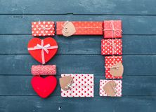 Valentines day composition: gift boxes with bows and hearts. Heart and gift boxes over wooden background. Flat lay Stock Photography