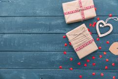 Valentines day composition: gift boxes with bows and hearts. On wooden background Stock Photos