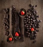 Valentines Day concept with chocolates, strawberry and spoon on. Wooden background from top view Royalty Free Stock Images