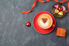 Valentines day concept with coffee cup, chocolate and gift box over dark background. Royalty Free Stock Image