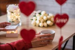 Free Valentines Day Concept. Cropped Of Lonely Woman Sitting On The Table Drinking Coffee With Bouquet Of Flowers Tulips Celebrating Royalty Free Stock Image - 170715686