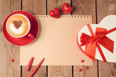 Valentines day concept with greeting card, gift box and coffee cup over wooden background. Top view Royalty Free Stock Photography