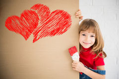 Valentines day concept. Happy child painting big red heart on the wall. Funny girl playing at home. Valentines day card. Renovation and design concept Royalty Free Stock Photo