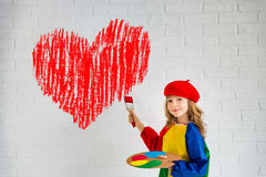 Valentines day concept. Happy child painting big red heart on the wall. Funny girl playing at home. Valentines day card. Renovation and design concept royalty free stock photography