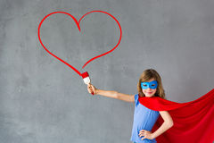Valentines day concept. Happy child painting big red heart on the wall. Funny superhero girl playing at home. Valentines day card. Renovation and design concept Stock Images