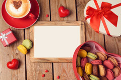Valentines day concept with macarons, coffee cup and blank photo frame over wooden background. Top view Royalty Free Stock Photos