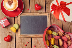 Valentines day concept with macarons, coffee cup and chalkboard over wooden background. Top view Stock Photos