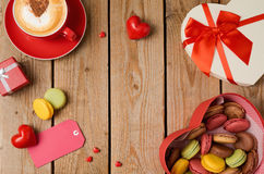 Valentines day concept with macarons, coffee cup and gift box over wooden background. Top view Stock Image