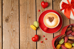 Valentines day concept with macarons and coffee cup over wooden background. Stock Images