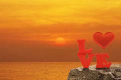 Valentines day concept. Red love alphabet and fabric heart ballon on rock over sunset sky and sea, Valentines day concept Stock Image