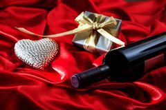 Valentines day. Red wine bottle, a gift and a heart on red satin. Valentines day concept. Red wine bottle, a gift box and a heart on red silk textile royalty free stock image