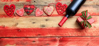 Valentines day. Red wine bottle, a gift and hearts on red wooden background. Valentines day concept. Red wine bottle, a gift box and hearts on red wooden royalty free stock photo