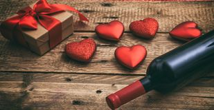 Valentines day. Red wine bottle, a gift and hearts on wooden background. Valentines day concept. Red wine bottle, a gift box and hearts on wooden background royalty free stock image