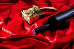 Valentines day. Red wine bottle and a gift on red satin. Valentines day concept. Red wine bottle and a gift box on red silk textile royalty free stock photography