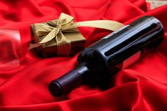Valentines day. Red wine bottle and a gift on red satin. Valentines day concept. Red wine bottle and a gift box on red silk textile royalty free stock images