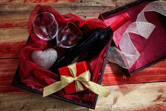 Valentines day. Red wine bottle, glasses and a gift in a box, wooden background Royalty Free Stock Photo