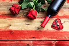 Valentines day. Red wine bottle and red roses on wooden background. Valentines day concept. Red wine bottle and red roses on wooden background stock images