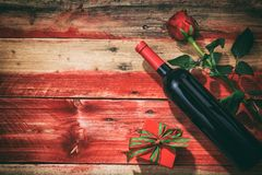 Valentines day. Red wine bottle, rose and a gift on wooden background Royalty Free Stock Photos