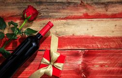 Valentines day. Red wine bottle, rose and a gift on wooden background Royalty Free Stock Images