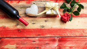 Valentines day. Red wine bottle, rose and a gift on wooden background. Valentines day concept. Red wine bottle, rose and a gift on wooden background royalty free stock image
