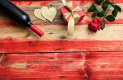 Valentines day. Red wine bottle, rose and a gift on wooden background. Valentines day concept. Red wine bottle, rose and a gift on wooden background stock images