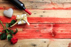 Valentines day. Red wine bottle, rose and a gift on wooden background. Valentines day concept. Red wine bottle, rose and a gift on wooden background stock image