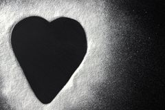 Valentines day concept white flour heart shape on black backround. Royalty Free Stock Photos
