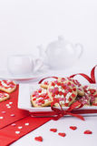 Valentines Day cookies, cup and teapot on white background. Heart shaped cookies decorated, teapot and cup Royalty Free Stock Photography