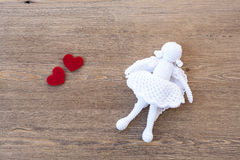 Valentines day crochet angel and two hearts on wooden table Stock Image