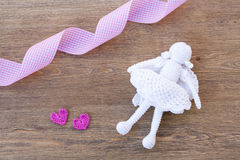 Valentines day crochet hearts and angel and ribbon on wooden table Royalty Free Stock Images