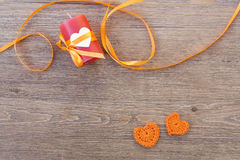 Valentines day crochet orange hearts, ribbon and candle on wooden table. Royalty Free Stock Image