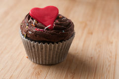 Valentines day cup cake with heart. Freshly made valentines cup cake lit by window light on wooden board stock image