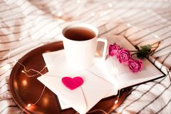 Valentines day with cup of tea. Romantic morning with cup of tea staying on open book with flowers in bed closeup. Valentines day stock photos